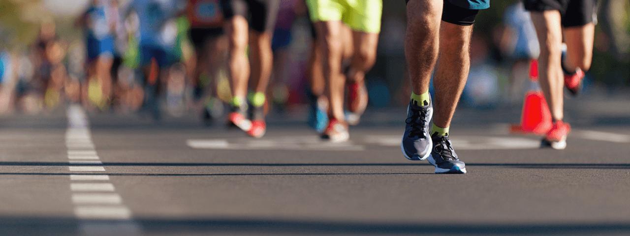 Bildausschnitt von Straße und Beinen laufender Menschen