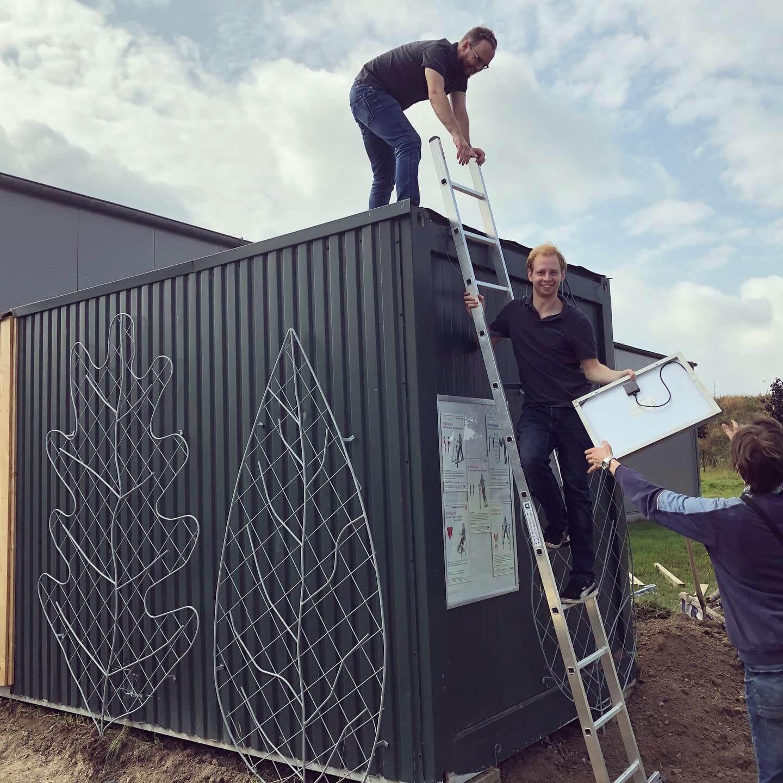 Mitarbeiter der PROSPER X GmbH beim Anbringen von Solar-Panelen auf dem Pausencontainer anlässlich der Aktion Brücken Bauen zusammen mit der Mehrwerk gGmbH