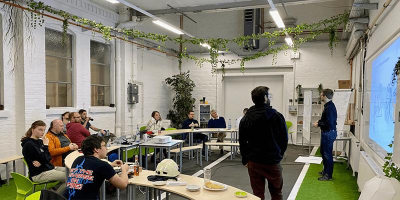 Mitarbeiter der PROSPER X GmbH hören der Präsentation auf Hackathon im Trafo Hub Braunschweig zu