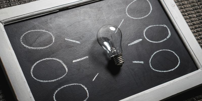 Schwarz-weißes Bild einer Glühbirne auf einer Tafel mit Kreidezeichnung als Symbolbild für Brainstorming