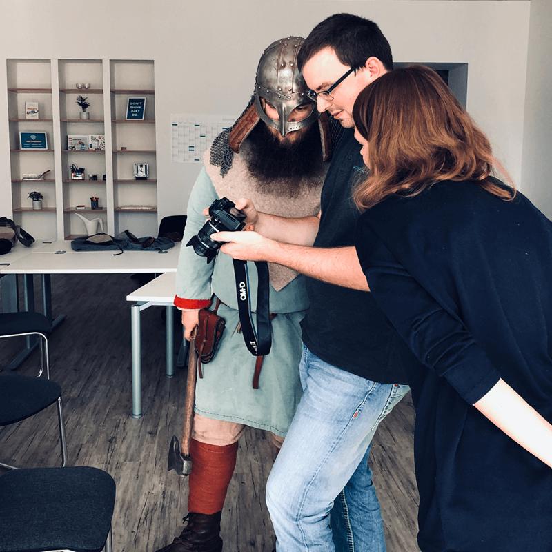 Im Rahmen unseres Fotoshootings sichtet ein Fotograf mit einer Person im Wikingerkostüm das Bildmaterial