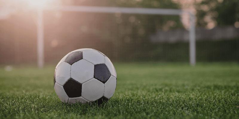 Fußball vor einem Tor auf einem Fußballplatz bei Sonnenuntergang