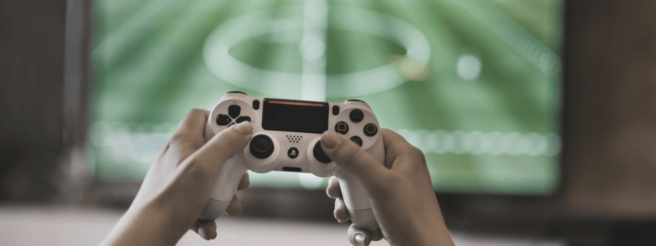 FIFA-Spieler mit PS4-Controller vor einem Bildschirm